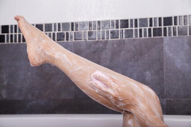 Femme lavant sa jambe avec du savon
