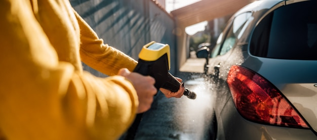 Femme lavant sa voiture avec nettoyeur haute pression
