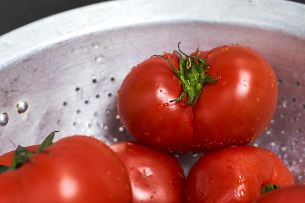 Femme lavant des tomates biologiques fraîchement cueillies dans une passoire