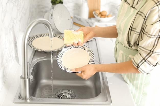 Femme lavant la vaisselle dans un évier de cuisine