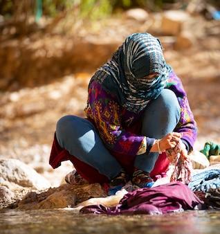 Femme lavant des vêtements dans la rivière des gorges pittoresques du dadès dans les montagnes de l'atlas