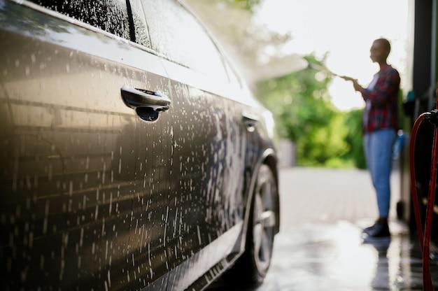 La femme lave la mousse de la voiture, lave-auto à la main