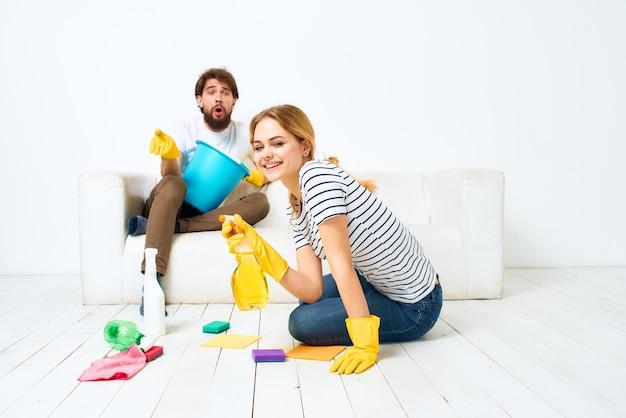 Une femme lave les sols pendant que l'homme est assis sur le canapé