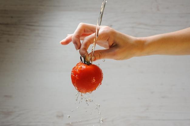 Femme lave une tomate