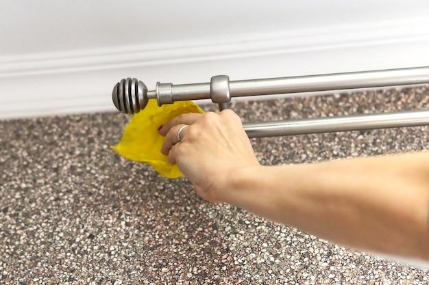 Femme lave une tringle à rideau en métal avec un chiffon jaune