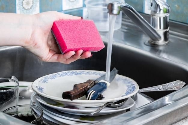 Une femme lave la vaisselle sale et tient dans sa main une éponge rose avec de la mousse.