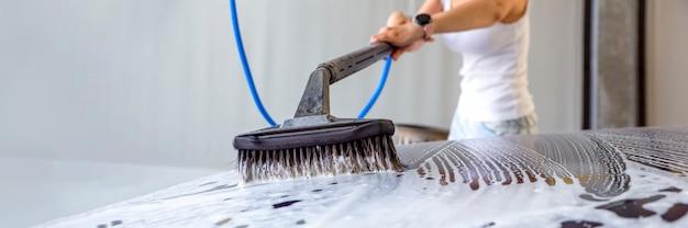 La femme lave la voiture. une femme à un lave-auto lave sa voiture avec une brosse avec du shampoing pour voiture. pour annoncer un lave-auto ou une bannière.