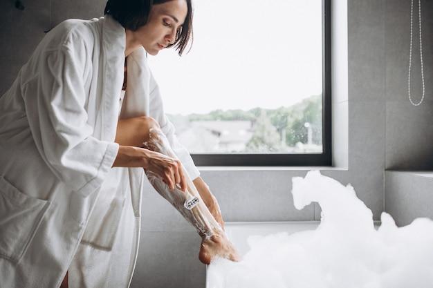 Femme laver les jambes à la maison dans la salle de bain