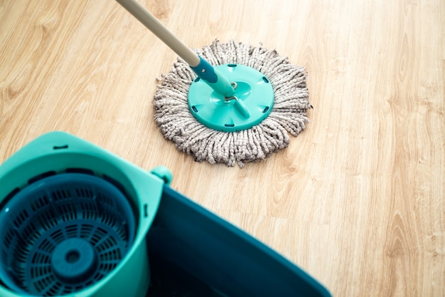 Femme, laver le plancher flottant en bois par une vadrouille, concept de nettoyage