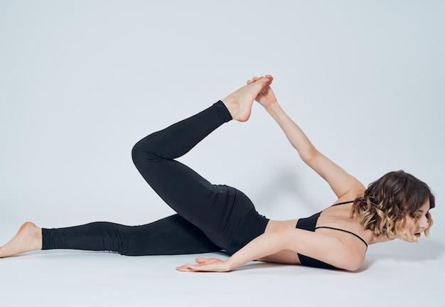 Une femme en legging noir est engagée dans la gymnastique dans une pièce lumineuse sur le sol.