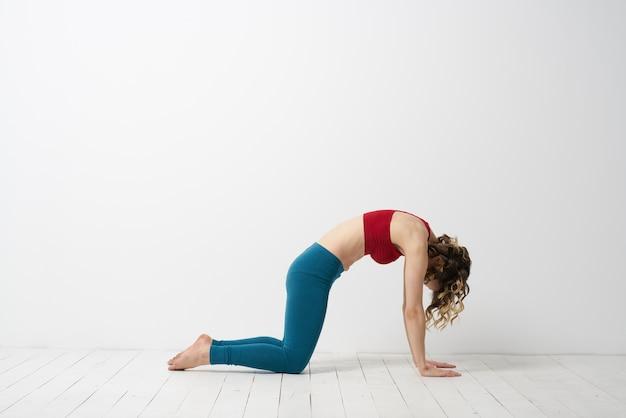 Femme en leggings est engagée dans la gymnastique dans une salle lumineuse sport de remise en forme mince.