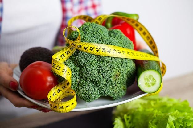 Femme avec des légumes dans ses mains avec un ruban à mesurer