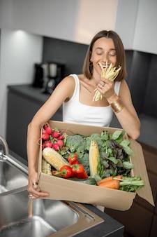 Femme avec des légumes frais emballés dans une boîte en carton à la cuisine