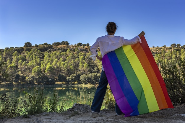 Femme lesbienne d'âge moyen méconnaissable tenant le drapeau gay arc-en-ciel au bord du lac à l'extérieur. notion de liberté