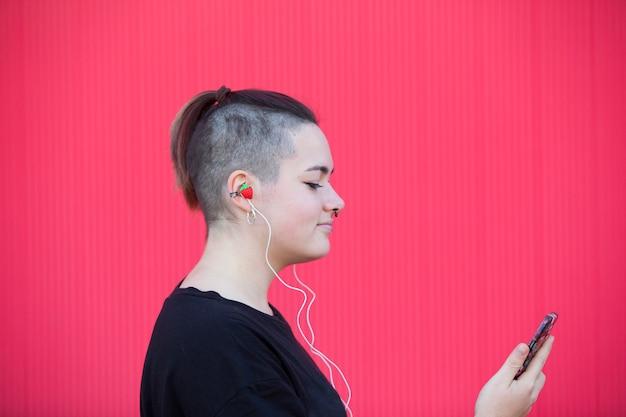 Femme lesbienne, écouter de la musique sur un mur rose