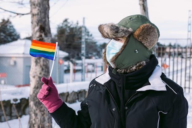 Femme lesbienne portant un bonnet de neige et un masque pour se protéger