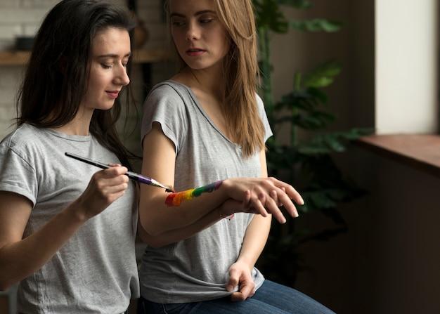 Femme lesbienne en train de peindre le drapeau arc-en-ciel sur la main de sa petite amie avec un pinceau