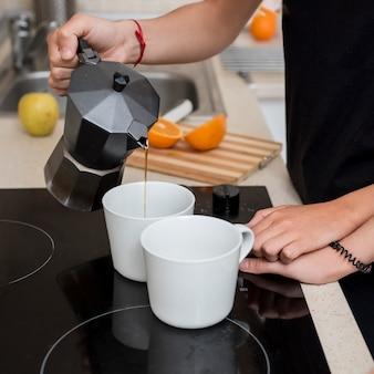 Femme lesbienne versant du café dans la cuisine