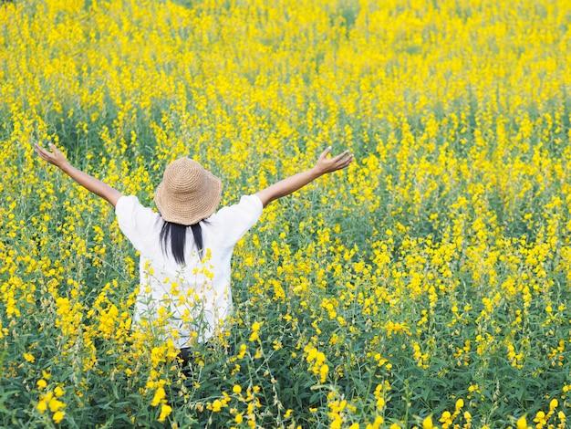 Femme levant les bras et debout dans le champ.