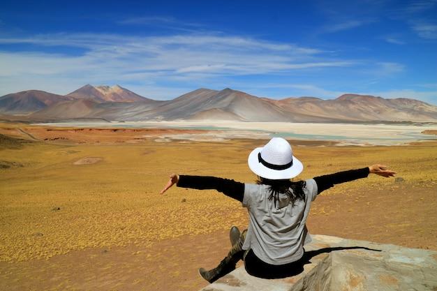 Femme levant les bras devant les lacs salés du salar de talar et la montagne de cerro medano, chili