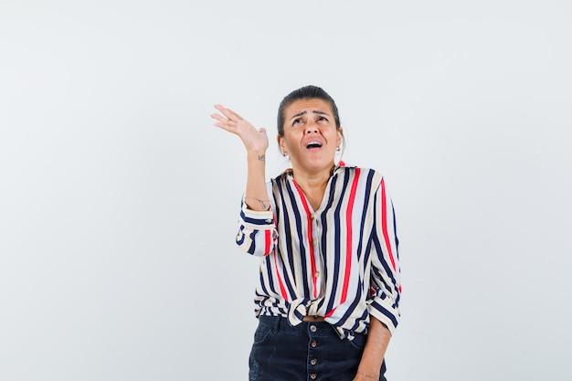Femme levant la main tout en regardant en chemise, jupe et à la recherche anxieuse.