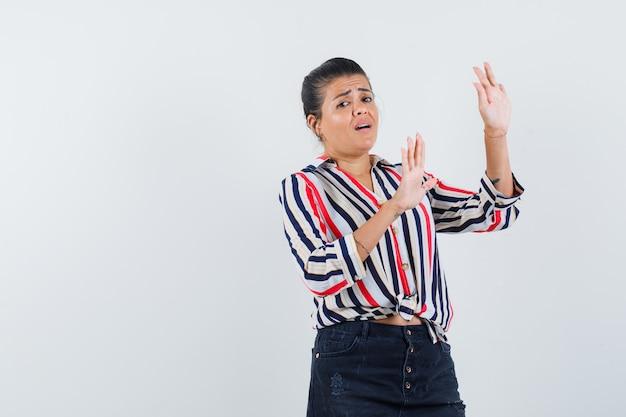 Femme levant les mains pour se défendre en chemise, jupe et à la peur.