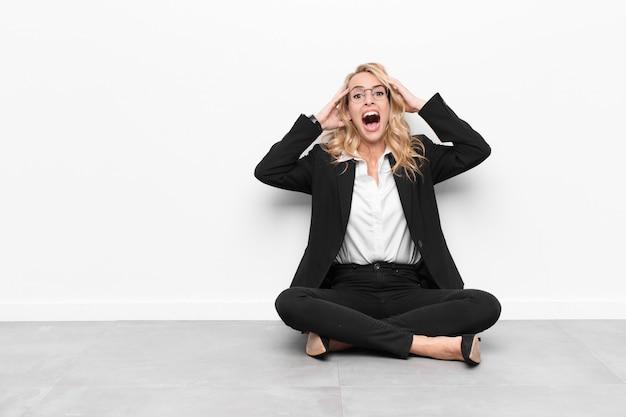 Femme levant les mains à la tête, bouche bée, se sentant extrêmement chanceuse, surprise, excitée et heureuse