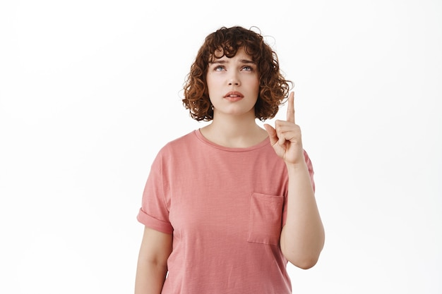 Femme levant les sourcils hésitante, pointant et levant les yeux avec un visage douteux, lisant l'espace de copie sur le dessus, debout en t-shirt sur blanc.