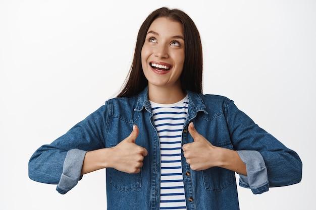 Femme, levant les yeux et souriant, montrant les pouces vers le haut, comme approuver, recommander le produit en haut, satisfaite des prix de vente, debout sur blanc.