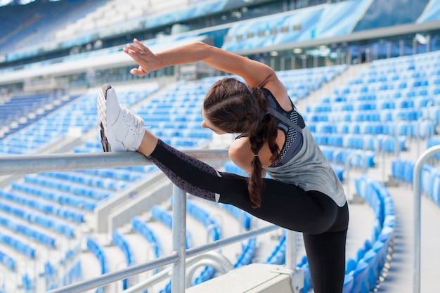 La femme lève la jambe dans le stade.