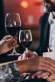 Une femme lève un verre et tient l'homme aimé par la main