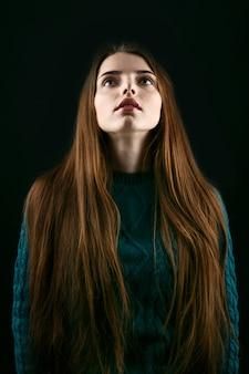 Femme avec des lèvres roses sensitives et de longs cheveux bruns lève les yeux dans le ciel
