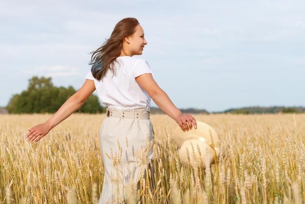 Femme libre et heureuse dans une robe volante et un chapeau sur un champ de blé. liberté, concept de joie.
