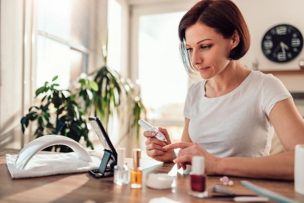 Femme limage des ongles avec une lime à ongles électrique et à l'aide de téléphone intelligent