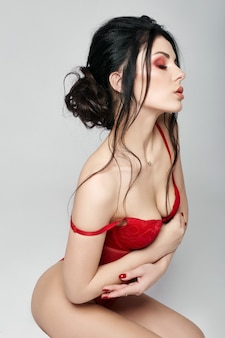 Femme en lingerie, fille sexy forte confiante. femme avec de beaux seins assis sur le sol