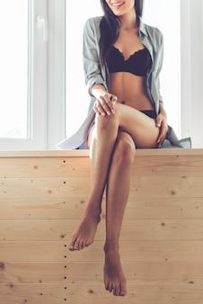 Femme en lingerie noire et chemise déboutonnée sourit.
