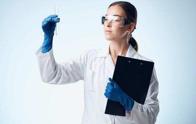 Femme avec un liquide dans un dossier d'élément chimique de recherche de laboratoire de fiole avec des documents