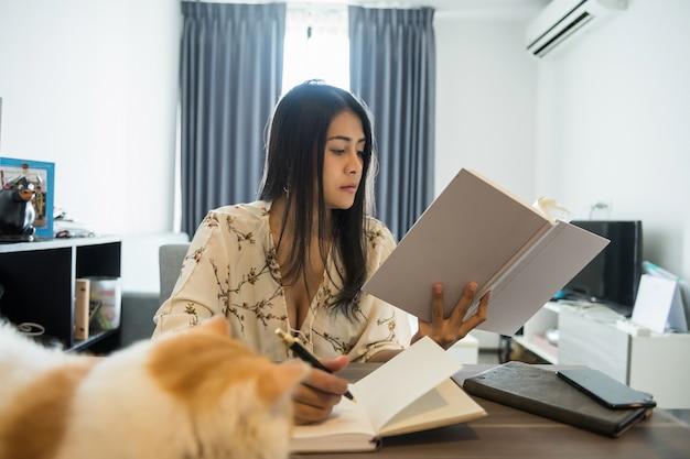 Femme lire livre et écrire du papier dans la chambre