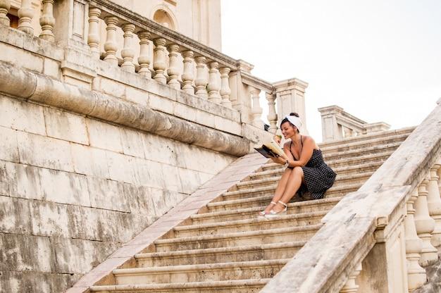 Femme lisant assis sur un ancien escalier de la ville
