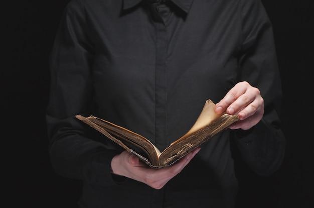 Femme lisant la bible dans le noir