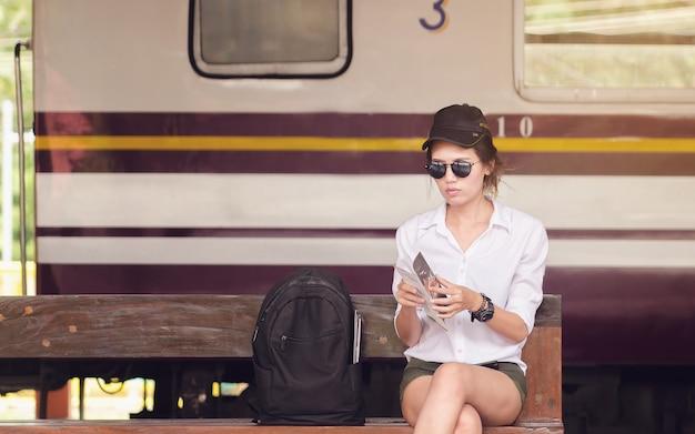 Femme lisant des brochures pour voyager. femme asiatique assise à la gare.