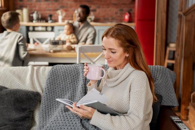 Femme lisant sur le canapé coup moyen