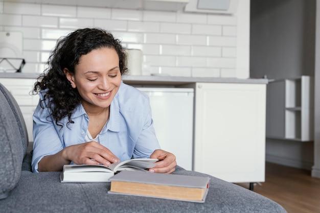 Femme lisant sur le canapé plein coup