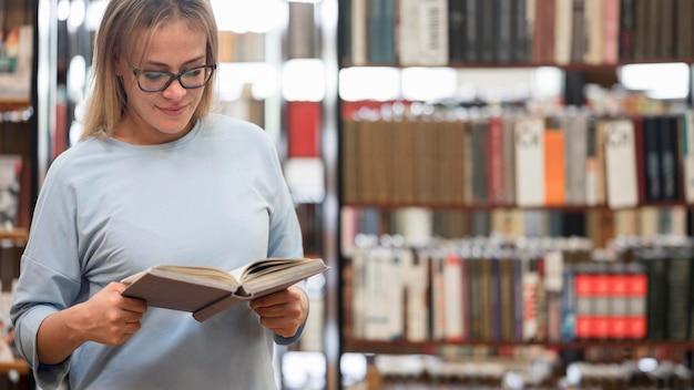 Femme lisant dans la bibliothèque coup moyen