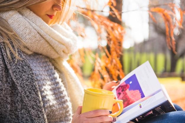 Femme lisant dans la forêt d'automne