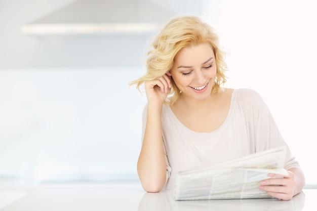 Femme lisant du papier à la maison le matin