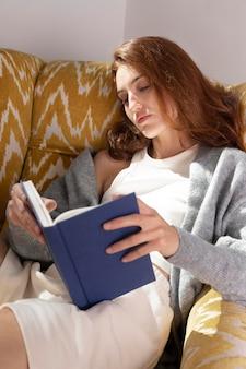 Femme lisant sur un fauteuil coup moyen