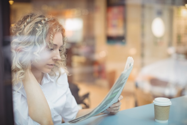 Femme lisant le journal au comptoir