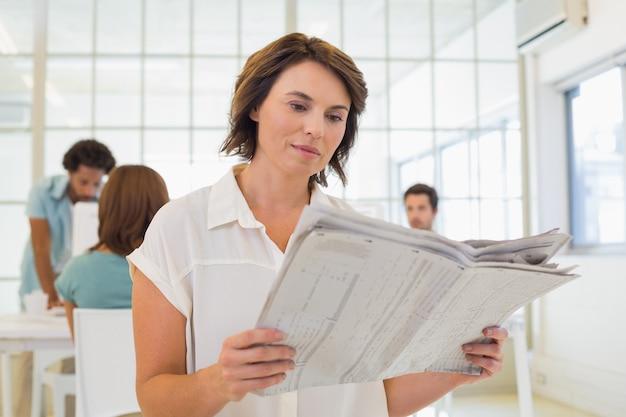 Femme lisant un journal avec des collègues en réunion