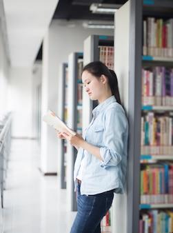 Femme lisant un livre appuyé sur une étagère